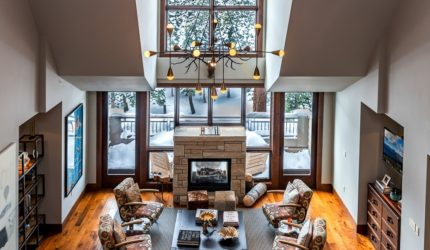 Upstairs view of Ritz Carlton Penthouse in Tahoe with hardwood floor, stone fireplace, vaulted ceilings, and gray walls