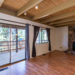 Family room with hardwood floor potbelly stove and back door leading to balcony on Park Lane in Tahoe