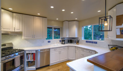 Kitchen with white cabinets and stainless steel appliances and bar counter