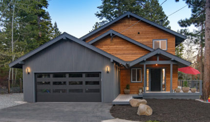 Front exterior of log cabin with gray garage