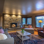 Low ceiling living room with large stone fireplace
