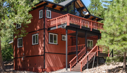 Exterior of red two story cabin with second story balcony and basement