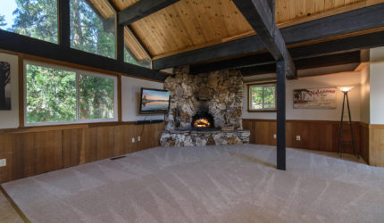 Large empty family room with large stone fireplace
