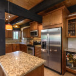 Intimate kitchen with tiled counters and wood real wood cabinets