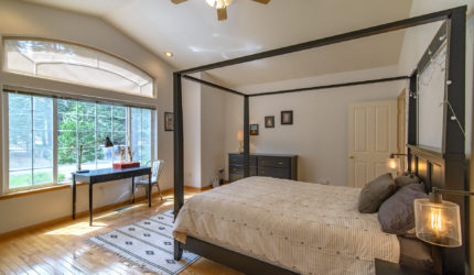 Master bedroom with wood floods and canopy bed