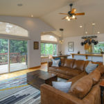 Family room leading to balcony with view of pines