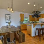 Kitchen with oak cabinets and flooring and large dining table